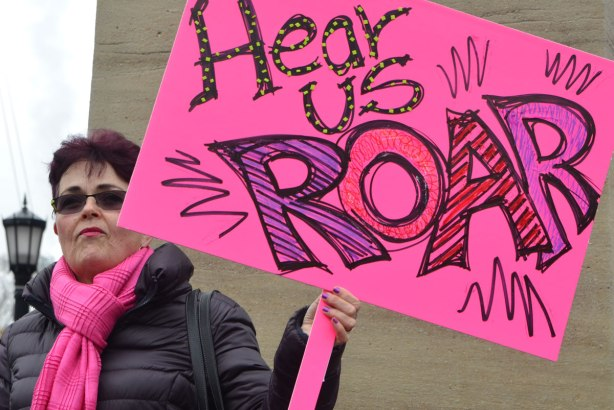 a woman stands beside the base of one of the statues at QUeens Park, she is holding a large pink sign with big colourful writing that says hear us roar. Womens March, toronto