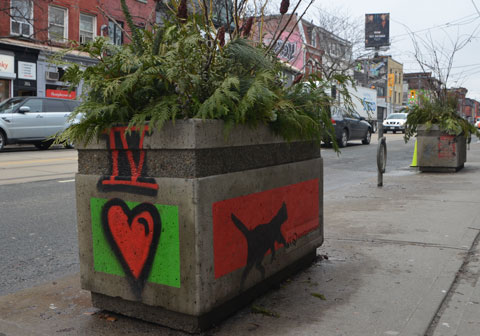 a rectangular cement planter on Queen Street west with pine and cedar boughs in it. The sides have been painted. On the end is the roman numeral 4 and a red heart. On the side is a black cat walking on a red background.