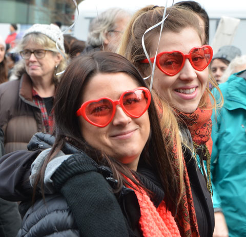 two women smile for the camera as they walk past. Both are wearing red heart shaped glasses.