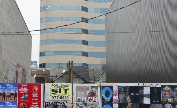 three layers, in the background a high rise building, in the middle ground, the tops of three single family homes on Richmond Street, in the foreground, poster covered hoardings for construction on Queen Stree West.