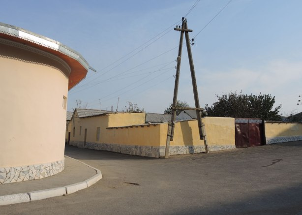 an intersection in Nurata Uzbekistan, a round building is on the left, a large hydro pole is in the picture but instead of a single pole it is two joined together at the top in an inverted V shape