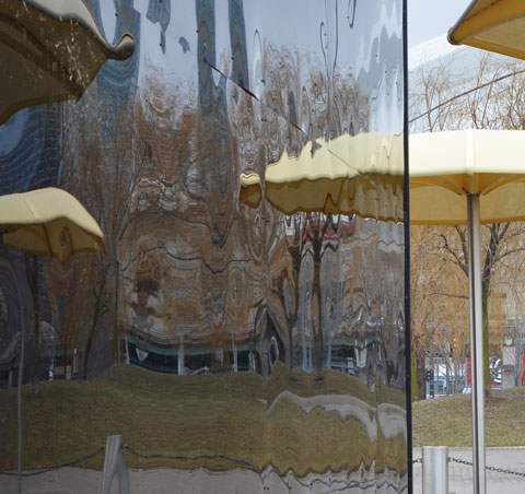 reflections of the yellow umbrellas of H T O beach on the black shiny sides of Icebox, an art installation at the beach