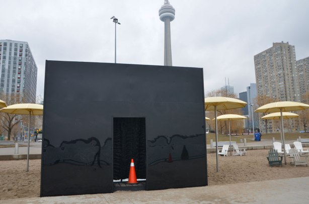 black box on a beach with muskoka chairs and yellow umbrellas,