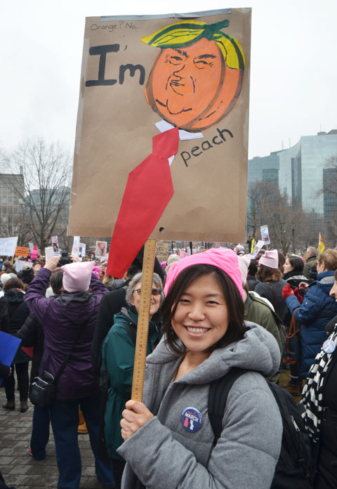 a woman is holding a sign at the Womens March, toronto . Donald Trump's head is shaped like a peach and the words say Im peach.