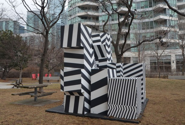 a public art installation in a park, winter time but no snow, no leaves on the trees, muddy brown grass, condo in the background. Artwork is a series of shapes stacked in a pile, all shapes are painted in black and white wide stripes. The stripes are horizontal, vertical and diagonal in the resulting structure, called incognito, by Jaspal Riyait and Curio