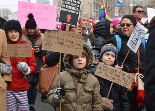 kids walking together in Womens March, toronto hold signs that they have made on cardboard.