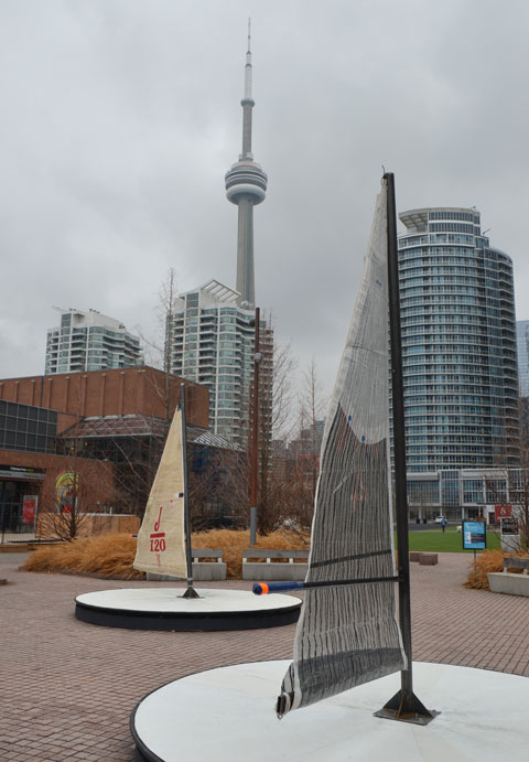 art installation beside Lake Ontario on Toronto's waterfront, called Leeward Fleet, by RAW consulting, two (of three) round platforms with a small sail in the middle. The boom of the sail is the handle for turning the platforms round and round like a merry go round. CN Tower in the background as well as some of the downtown condos.