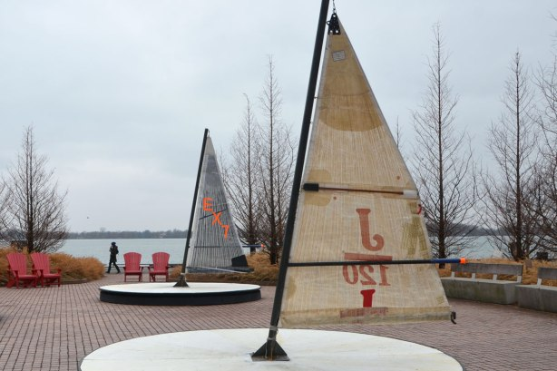 with the lake in the background, art installation beside Lake Ontario on Toronto's waterfront, called Leeward Fleet, by RAW consulting, two (of three) round platforms with a small sail in the middle. The boom of the sail is the handle for turning the platforms round and round like a merry go round.