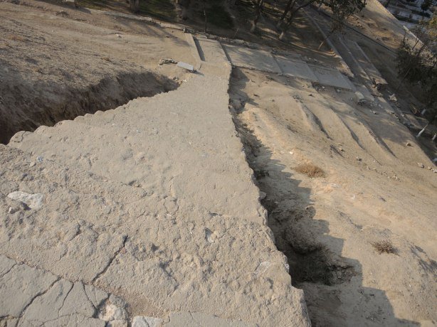 looking down a very steep set of stairs roughly hewn in the dirt and rock of the hill