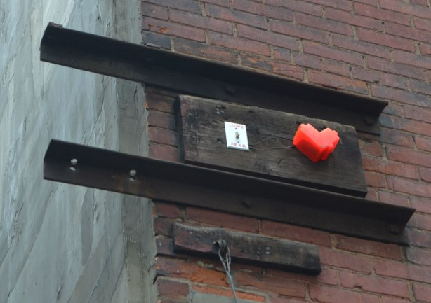 high on a wall, a small 3D lovebot heart beside a light switch that is love on one side and fear on the other.
