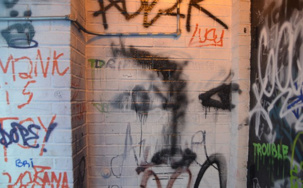 in a dimly lit doorway, a lot of scribbles and graffiti including a roughly drawn face, the word Lucy and the word trouble