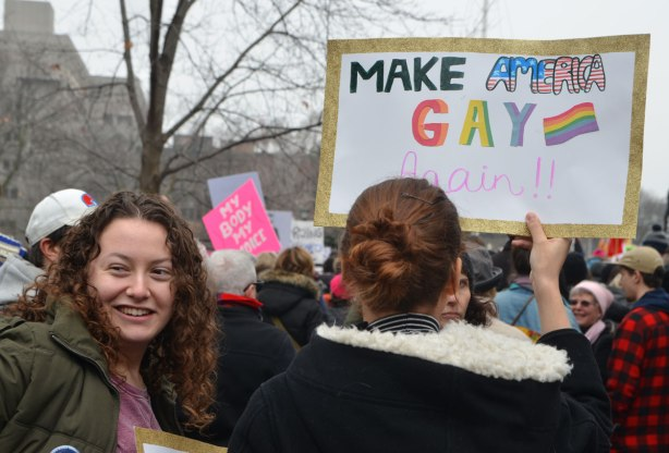 A woman holds up a sign that says Make America Gay again. Lots of other people around her at Queens Park at the start of the Womens March, toronto