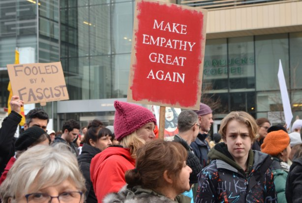 a woman walking in the Womens March, toronto holds up a read sign that says Make Empathy great again. Lots of other men and women walking in the same picture.