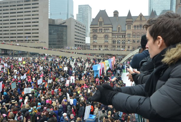 Taken from the upper level at Nathan Phillips Square, overlooking the square which is full of people attending Womens March, toronto . In the foreground are a couple of people who are also on the upper level.