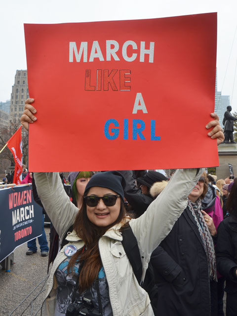 a woman holds up a red sign that says March like a girl, Womens March, toronto