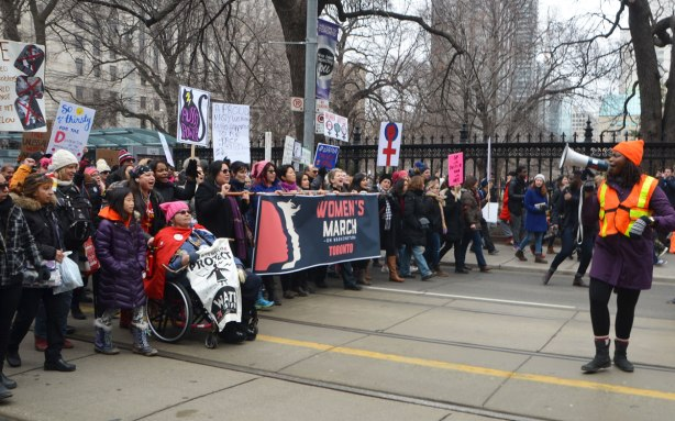 Womens March, toronto - the head of the march goes past Osgoode Hall on QUeen Street. A woman with a megaphone is leading the chants and singing. A large group with a banner that says Womens March is the first group in the walk