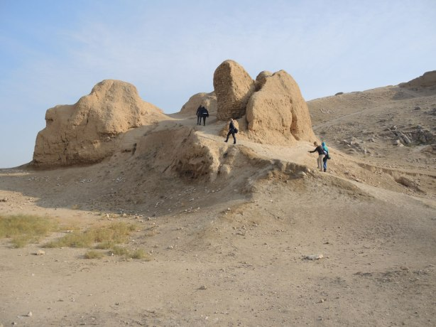 the remains of the fortress built by Alexander the Great, with some people climbing up to take a look at it.