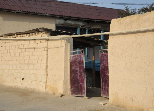 street in Naruta Uzbekistan with yellowish coloured mud walls lining the street - an old metal gate that was once painted maroon, the blue of the entranceway to the house beyond the gate