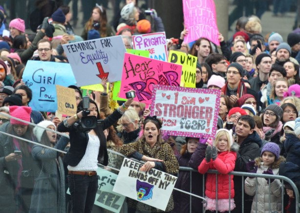 standing behind the barricades by the stage at Nathan Phillips Square, a large group of people at the Womens March, toronto . Many signs and many people. and a reporter with a camera.