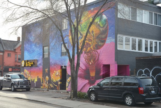 large mural of a honey bee on a big pink flower hibiscus, with other yellow flowers growing, also a black skyline of Toronto, a large tee grows in front of the building and a van and a truck are parked close by. Photo taken from across the street.