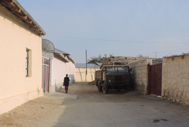 street in Naruta Uzbekistan with yellowish coloured mud walls lining the street - a woman walks up one side of the street, past a green truck parked on the other side of the street