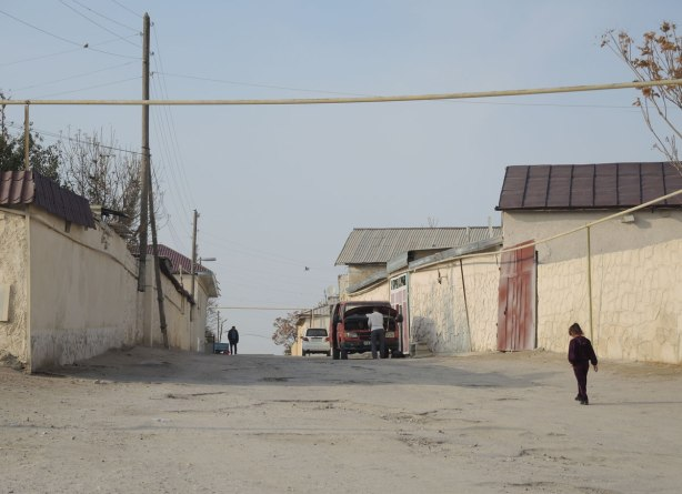 street in Naruta Uzbekistan with yellowish coloured mud walls lining the street - a man is working on a red van parked at the side of the street, a child is walking up the street