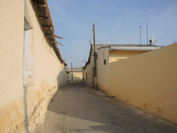 street in Naruta Uzbekistan with yellowish coloured mud walls lining the street - narrow street, dirt