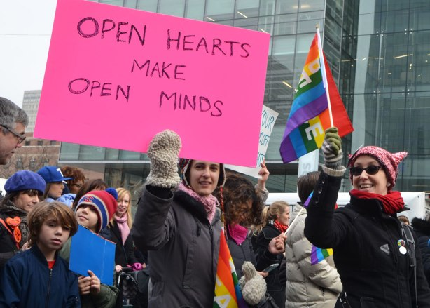 a young woman holds up a large pink sign that says open hearts make open minds. Womens March, toronto