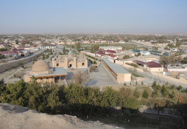 the view of Nurata from the hill where Alexander the Great built his fortress. low rise buildings, a mosque with a dome, a few trees, and the desert beyond.