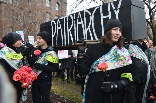 a group of people wearing black and holding red carnations is holding a large black coffin on their shoulders. Written on the coffin is the word patriarchy. The death of patriarchy.