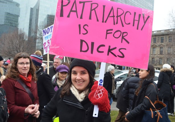 a woman holds a sign that says patriarchy is for dicks
