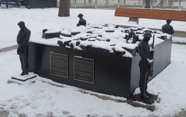 a sculpture called Peace Through valour by Ken Lum, outside on a snowy day. A square piece with a soldier standing guard at each corner. On top of the flat squsre is a model of a town in square blocks (no details on the buildings).