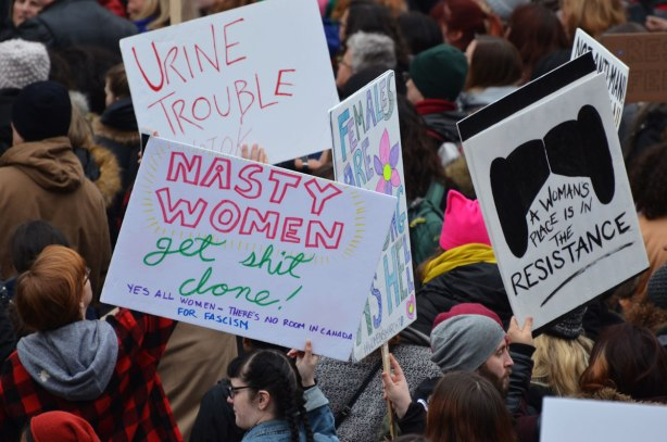 a group of people with signs and placards in a crowd at Nathan Phillips Square. Womens March, toronto