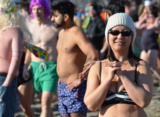 people participating in the 12th annual polar bear dip at Sunnyside Park in Toronto, in the icy cold water of Lake Ontario