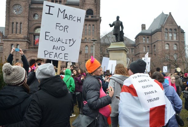 In front of the building at QUeens Park, a large group of people has congregated for Womens March, toronto . One woman holds a sign that says I march for equality and peace. Another woman has a flag draped over her back with says I'd rather have a queen than a trump