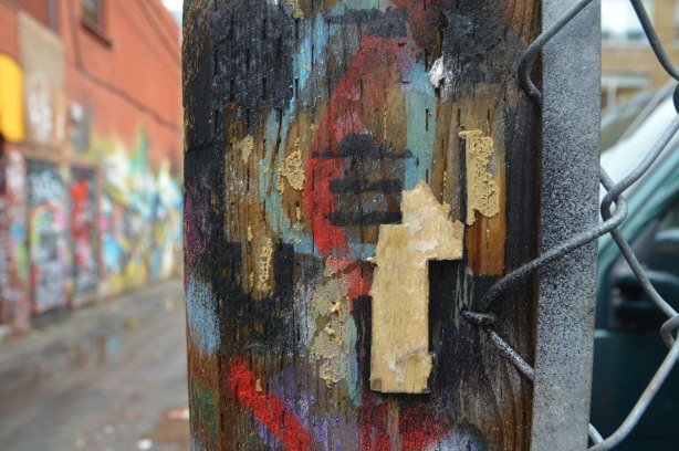 a tiny bit of a stikman is left on a post that is covered with spray paint.
