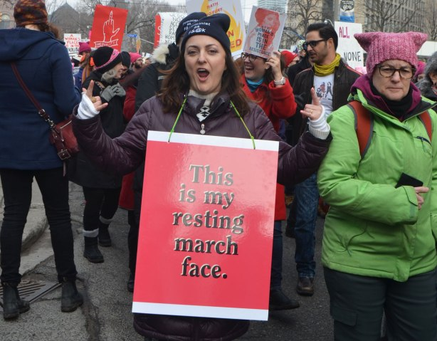 Womens March, Toronto, a woman with a red sign saying This is my resting march face, hams it up for the camera