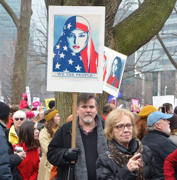 "a man holds a sign up in the air, above the heads of out protesters at the Womens March, a Shepard Fairey design of a woman in stars and stripes American flag head scarf withthe words ""We the People"""