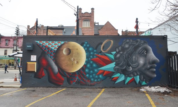 birdo mural on the side of a building, a red high heel shoe, a brown circle, a grey head plus the colourful geometric shapes often found in a birdo mural, in reds and turquoise