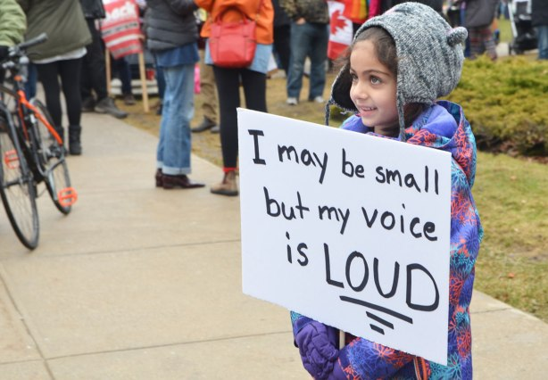 Womens March, Toronto, a young girl in a grey hat holds a white sign that says I may be small but my voice is loud.