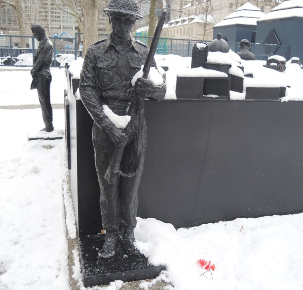 two soldiers stand vigil at the corners of a memorial, sculptures,