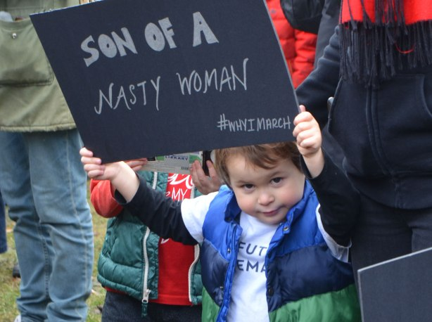 a boy holds up a sign that says Son of a Nasty Woman, #whyimarch, Womens March, toronto