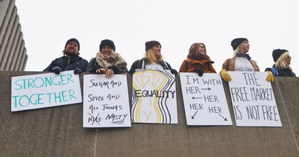 Womens March, toronto - a group of people leaning over the edge of the upper level at Nathan Phillips, holding their placards and signs over the concrete. Two of the women are wearing white T-shirts on which they've drawn black outlines of breasts.
