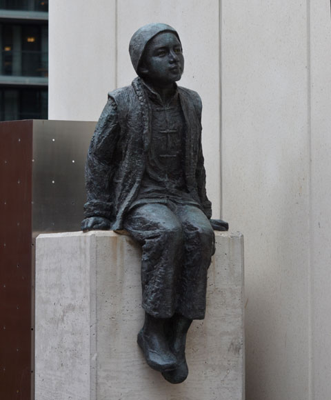 sculpture, Two Children of Toronto by Ken Lum in a downtownwalkway with a concrete bulding beside it, a boy is seated on a concrete pedestal.