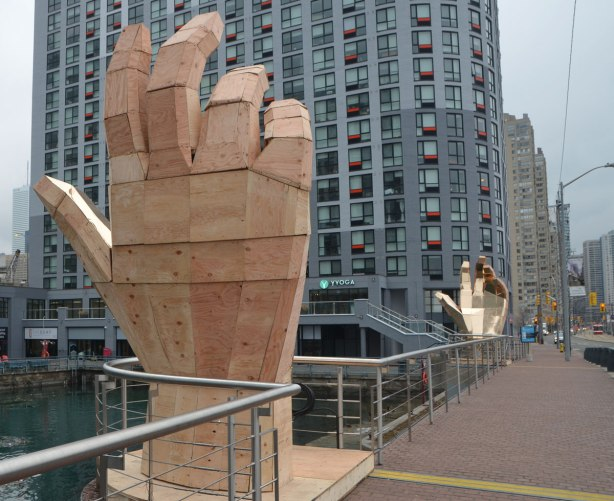 two large wooden hands face each other, beside the sidewalk, condos behind, the plams are covered with shiny gold,