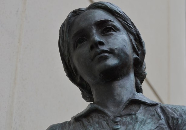 sculpture, Two Children of Toronto by Ken Lum in a downtownwalkway with a concrete bulding beside it, girl's face