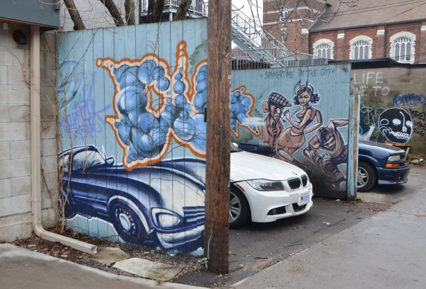 in an alley, a white car is parked between a blue car and a mural painting of a blue car. There is also a mural of three people with the words summertime in the city.