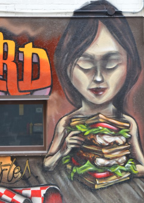 from a mural by elicser along the exterior wall of the dirty bird chicken and waffle restaurant - a woman is sitting at a table in the restaurant with a very tall chicken and waffle sandwich in her hands