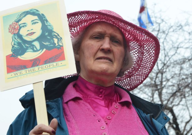 an older womaloosely woven pink hat with wide brim, and a pink top, holds a sign at a march