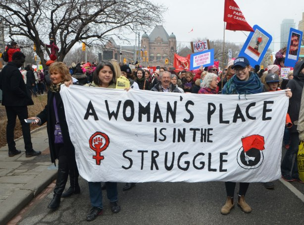 a group holds a white banner as they walk in the Womens March, the banner says A woman's place is in the struggle.